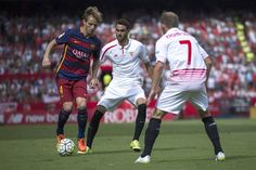 Ivan Rakitic (L) of FC Barcelona competes for the ball with Vicente Iborra (2ndR) and his teammate Michael Krohn-Dehli (R) during the La Liga match between Sevilla FC and FC Barcelona at Estadio Ramon Sanchez Pizjuan on October 3, 2015 in Seville, Spain.