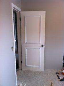 Easy update to plain doors: white paint, wood wall trim, and oil rubbed bronze spray paint on the knobs