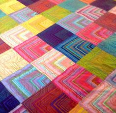 This is a double sized quilt in a chevron design. It has a bright rose floral backing with an added row of log cabin blocks through the middle. The fabrics are from Kaffe Fassett ,whom I love. His colors are so beautiful.