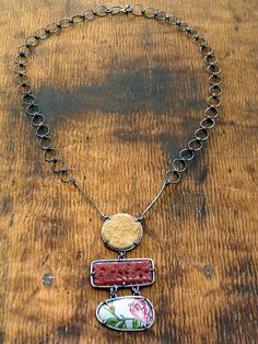 Maria Whetman: cast glass cabochon, reclaimed, Italian biscuit tin, leather..........WOW, look at that chain!!