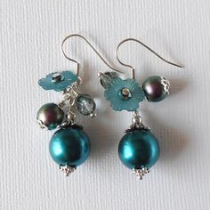 Fun and flirty jangly dangle earrings in a pretty shade of teal include large glass pearls, lucite flowers with faceted glass bead centers, light aqua faceted Czech glass beads and peacock round glass beads. Ive dressed up some of the beads with silver plated beadcaps and spacer beads. Beads are threaded on silver plated pins and all are secured with wrapped loops. The earring wires are silver plated hooks. Please see photo #5 for length measurement. *********************************...