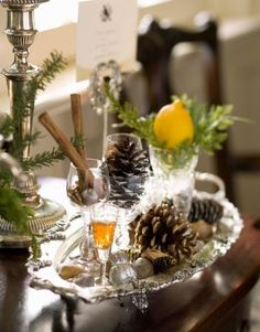 Small vignettes, such as this one with pinecones, nuts and cinnamon sticks in crystal apéritif glasses on a silver tray, add surprising and sparkling detail to a room. More ideas from Nell Hill: http://www.midwestliving.com/homes/featured-homes/holiday-house-tour-at-home-with-nell-hills-owner/page/3/0