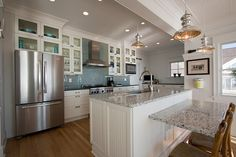 white cabinetry with glass doors, recycled glass countertop, attached bar.  Nat's favorite kitchen