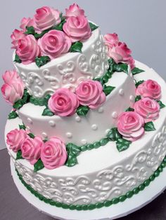Pink sprayed roses, green leaves & beading & white scrolling on our fondant iced cake