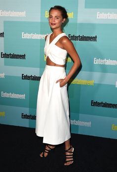 Alicia Vikander wears a white crop top with white culottes and strappy heels
