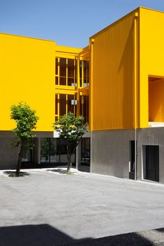 Aurora Arquitectos connects classroom blocks with bright yellow stair tower