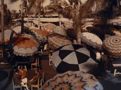 """n this Autochrome image from a January 1930 National Geographic story on Florida, colorful umbrellas shade members of an oceanfront club in Miami Beach. They """"bathe in the blue, sunlit Gulf Stream,"""" says the picture's caption, """"and enjoy other healthful exercise when the northern resorts are icebound."""