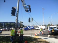 """Their goal: reconnect the traffic signal to its pole and get it back into the ground. Having removed the fixture to make way for the shuttle, the workers' neon vests appropriately read """"Shuttle Delivery Team."""""""
