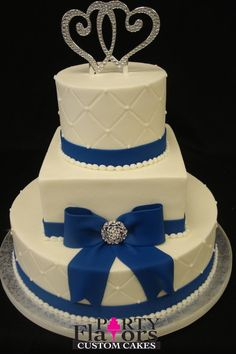 A simple and classic white wedding cake gets an upgrade with a navy fondant bow and crystal brooch. The metallic intertwined hearts are the perfect topper!