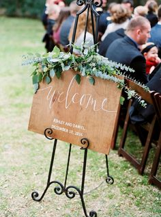 A rustic welcome sign with custom white calligraphy and topped with decorative greenery greets guests as they arrive at the outdoor wedding ceremony near Austin, Texas // Jen Dillender Photography