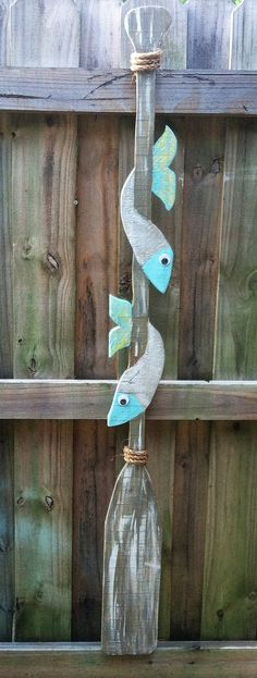 Decorative Wood Oar Art. I cut this from one piece of wood. Sanded, stained and painted, then trimmed with rope. Each fish has a google eye! $42 Available at: https://squareup.com/market/junk-drunk-repurposed-stuff/ Thanks for lookin' :) SORRY, SOLD!! I take custom orders, so contact me if you would like a special decorative oar!