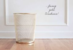 Spray paint a cheap metal trash can with gold spray paint for a chic high end look.  She used Rustoleum spray paint in brass, which actually goes on more like gold.