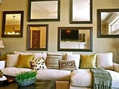 A collection of mirrors hung gallery style, above the overstuffed sofa, is the perfect alternative to art. Adding this many mirrors to one wall also amplifies the natural light. Design by HGTV Star winner Tiffany Brooks