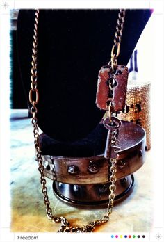 A long chain with a piece of salvage hardware and antique key that hang off to the side.