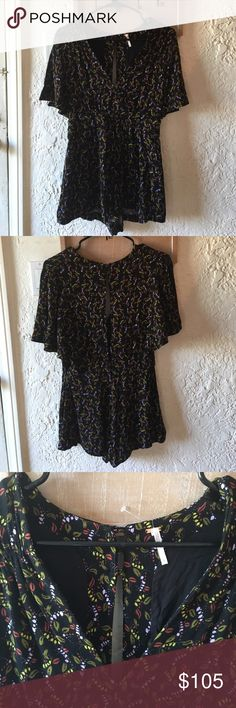 Beautiful Free People romper 🌺 NWT 🌺 This is a lovely little romper with black background and a color palette which includes: maroon, lavender, yellow and a muted green. The pattern is consistent and floral but in a subtle way. There's a deep V neckline, split short sleeves and is partially lined. In back, there's a long tasteful cutout flanked by delicate buttons above and below. For Autumn, throw on a solid cropped cardigan or lil jean jacket and a pair of high boots! For summer, strappy…