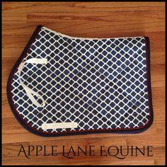 Custom navy/white lattice saddle pad with red braid trim by Apple Lane Equine. Www.applelaneequine.com