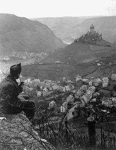 This old castle perched on a hilltop above the Moselle River and the town of Cochem, Germany, is headquarters of the U.S. Fourth Army Corps. In foreground is Cpl. James C. Sulzer, Fourth Army Corps. January 9, 1919. by Sgt. Charles E. Mace.