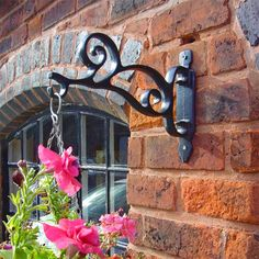 Scroll Hanging Basket Bracket - A very strong, sturdy and practical hanging basket bracket with a simple stylish scroll design. Made from solid cast iron and coated in a tough yet beautiful weather proof coating in black to last a lifetime