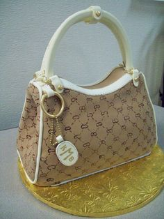 """3D  Gucci Purse Cake finished with Rolled Fondant.  Hand made handles and gold accessories as well as a Painted design on the """"leather""""."""
