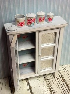 Decoupaged roses into metal canisters for shabby chic dollhouse