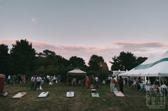 guests playing outdoor lawn games at dusk in friends and family farm during wedding reception