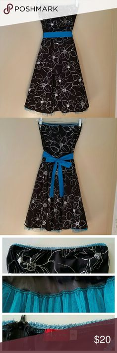 SALE Black and White Floral Strapless Dress This black and white floral strapless dress has a removable blue sash that can be tied in front, back or side depending on your preference. There is a matching blue tulle petticoat sewn onto the slip underneath.  Dress is Juniors size 3 and measures approximately 33 in. long from front top to bottom of tulle skirt. Approximately 12 in. from armpit to armpit but will stretch to around 16 in. due to elastic top.  A few small stains/spots and hole in…