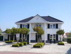 Witte villa met zwarte luiken en deuren