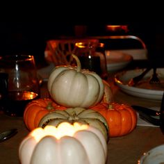 Hollow out mini pumpkins and drop in tea nights for a quick centerpiece down the middle of the table.