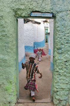 Boy crossing a door frame in Harar, Ethiopia