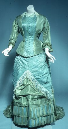 Dress Date: ca. 1870–1880 Media: Pale Olive Green Taffeta, Damask, And Sateen Accession Number: 52.12.1a-b Cuirasse style bodice, central panel of figured blue-green silk, attatched lace collar. Overskirt of figured silk attatches to bodice and is elaborately draped at the back. Trimmed with chenille fringe. Underskirt of olive taffeta, ruched, trained and trimmed with pleated flounces. For a large bustle.