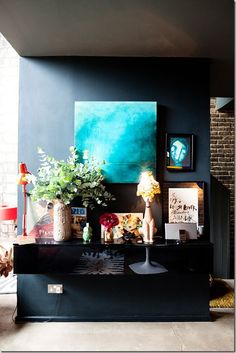 dark accent wall with turquoise painting