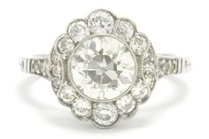 """The Anaheim Art Deco 1.58 carat old European diamond oval halo flower cluster engagement ring is a dynamic and breathtaking bridal masterpiece. Centered by a sparkling old """"Romance Stone"""" with those chunky facets that twinkle under a candle's glow set securely in a hand made platinum setting adorned with a milgrain accented bezel. #engagementring #artdeco diamond #platinum #love #ido #engaged #artdecoring #artdecorings #santabarbara #bellarosagalleries #engagementrings #oldeuropeandiamond Estate Engagement Ring, Antique Engagement Rings, Oval Diamond, Diamond Bands, Art Deco Ring, Conflict Free Diamonds, Halo, Target, Hand Making"""