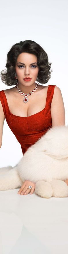 Looking firery, this glamour girl wears a slendid red dress with a white fur wrap. (Vogue)