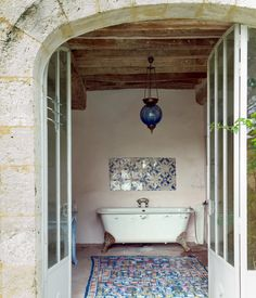 a bathroom furnished with an antique tub, a hanging lamp the couple found at a bazaar in Turkey and a Tunisian rug.