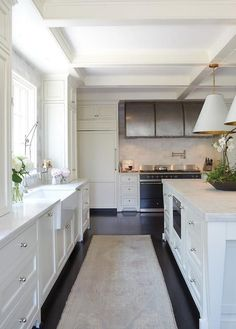 A gorgeous faded vintage rug sits on an ebony wood floor in front of a farmhouse sink fixed beneath a window to white shaker cabinets adorned with polished nickel knobs.