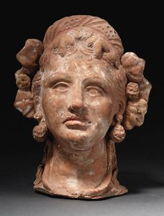 A GREEK TERRACOTTA INCENSE BURNER   canosan, circa 3rd century b.c.   In the form of a woman's head, wearing large stippled earrings in the form of double lion heads, a thick fillet with ivy leaves and berries in her wavy hair, with tendrils of hair falling along the neck, behind the spiral necklace, the head perhaps originally surmounted by a calyx of leaves, with traces of polychromy throughout