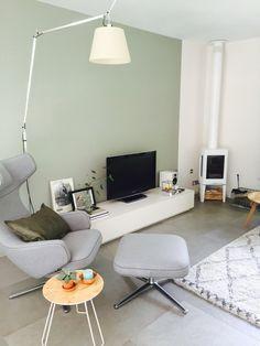 De grijs-groene kleur op de muur en kachel is ook leuk