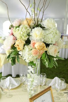 Wedding centerpiece idea - Soft palette of ivory, peach and pale yellow.