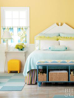 Daisy-yellow walls create a happy background for this welcoming bedroom. Softened by white woodwork, beaded-board wainscoting and headboard, and a whitewashed pine floor, the yellow makes a sunny statement reiterated by the charming little footstool. To cool down the sunshine color, baby blue, azure, and apple green complete the color palette in the bedding, cafe curtains, bench, and rug.