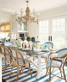 Gorgeous beach house dining space featuring French style blue and white wicker chairs and sea shell chandelier... House of Turquoise: Ashley Whittaker Design