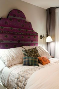 Bare walls create space whilst patterned headboard and comfy cushions add colour becoming the main design focus