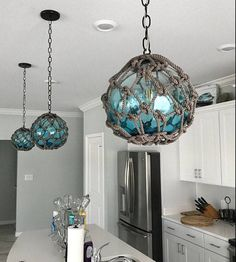 These are beautiful and unique pendant lights made from glass fishing floats with netting. The glass floats come in different colors and the height/length of the electrical cord can be adjusted to suit your needs. DIMENSIONS: Glass floats are approximatel Nautical Lighting, Coastal Lighting, Coastal Decor, Coastal Cottage, Nautical Chandelier, Coastal Light Fixtures, Coastal Curtains, Coastal Entryway, Wooden Chandelier