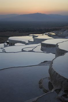 """Pamukkale, meaning """"cotton castle"""" in Turkish, is a natural site in Denizli Province in southwestern Turkey. The city contains hot springs and travertines, terraces of carbonate minerals left by the flowing water. It is located in Turkey's Inner Aegean region"""