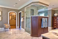 Wood paneling warms up this luxurious glass and marble walk-in shower, part of a spacious master suite. A tall wood dresser provides elegant storage in the corner.