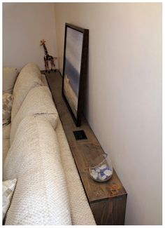 a shelf and an electrical outlet behind a couch.  http://turtlesandtails.blogspot.ca/2013/03/diy-sofa-table.html