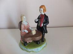 PAR DE MÚSICOS EM FAIANÇA Estatueta exibindo um par de músicos (pianista e violinista), em faiança. Não marcada.  Dimensões: 12x18x10 cm