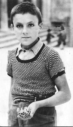 An Eight-year-old Italian boy holding a handful of detonators he had removed from German hand grenades. Italy, 1944.