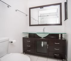 A beautiful modern bathroom with a custom vanity and white floor tile
