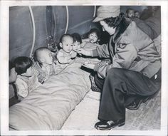 A US Army nurse, dressed in a USAF jacket, in 1951 feeding Korean orphans