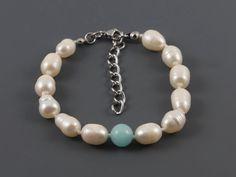 Náramek bílé perly a amazonit LI440. Jedinečný náramek s bílými perlami. Náramek je vyroben ze šlechtěných sladkovodních perel o velikosti cca 10 mm a amazonitů o průměru 8 mm; perly jsou mezi sebou navázany uzlíkovou metodou. Délka náramku je 18 - 22 cm. Barva perel je bílá krémová s přirozenými odlesky. Náramek byl vyroben v České republice.